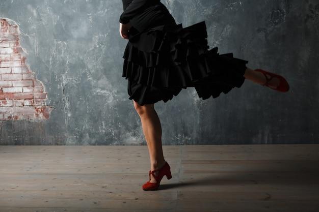 Junge erwachsene spanierin tanzt flamenco auf grauem vintage-studio-hintergrund