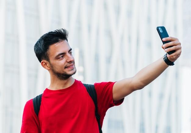 Junge erwachsene studentin, die ein selfie mit einem mobiltelefon vor einem unscharfen städtischen hintergrund macht