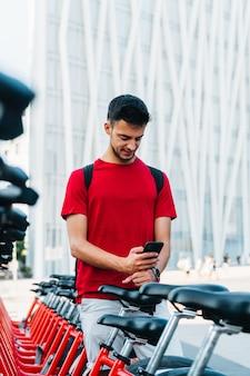 Junge erwachsene studentin mit einem handy auf einem gemieteten fahrrad