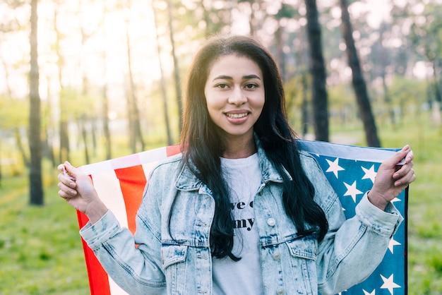 Junge ethnische frau, die mit amerikanischer flagge aufwirft