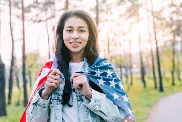 Junge ethnische frau eingewickelt in der amerikanischen flagge