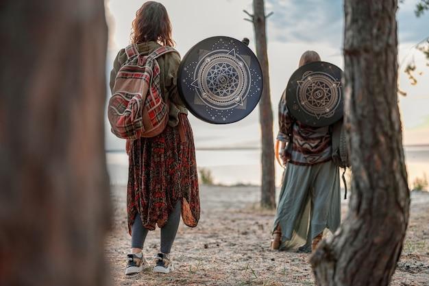 Junge ethnische reife schamanin geht und spielt schlagzeug meditative musik