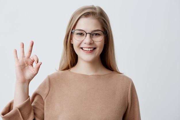 Junge europäische blonde frau, die ok-geste mit ihren fingern zeigt. glückliches mädchen im braunen pullover und in den brillen breit lächelnd. ihr fröhliches gesicht beweist, dass alles nach plan läuft