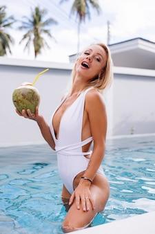Junge europäische blonde haare passen frau im weißen badeanzug steht in hellblauer farbe schwimmbad natürliches tageslicht hält kokosnussplastikstroh