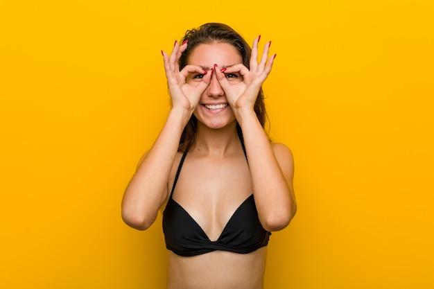 Junge europäische frau, die bikini trägt, der okay zeichen über ihren augen zeigt