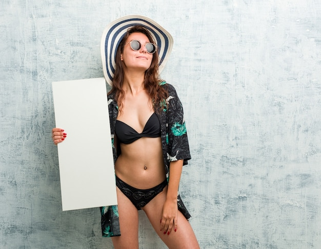 Junge europäische frau, die bikini trägt und ein plakat hält