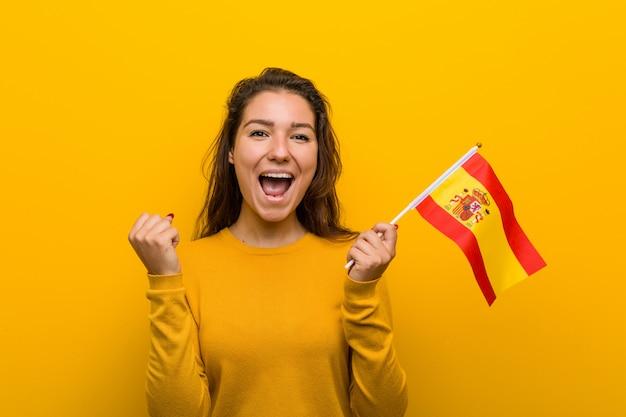 Junge europäische frau, die ein spanisches markierungsfahnenzujubeln sorglos und aufgeregt anhält.