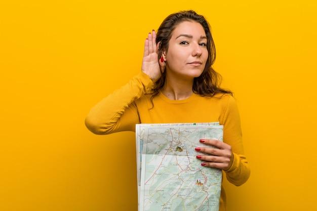Junge europäische frau, die eine karte versucht, einen klatsch zu hören hält.