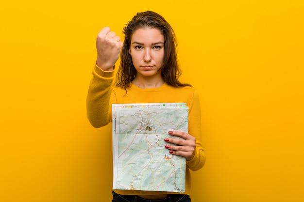 Junge europäische frau, die eine karte zeigt faust zur kamera, aggressiver gesichtsausdruck hält.