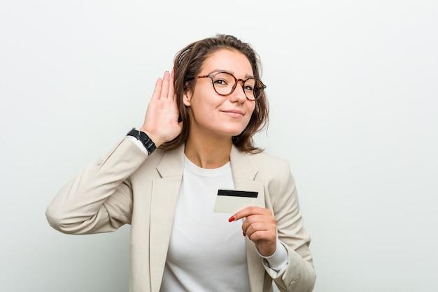 Junge europäische frau, die eine kreditkarte versucht, einen klatsch zu hören hält.