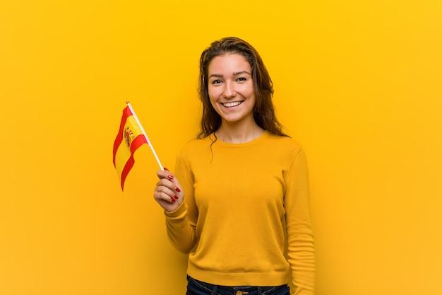 Junge europäische frau, die eine spanische flagge glücklich, lächelnd und nett hält.