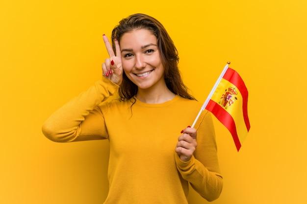Junge europäische frau, die eine spanische flagge hält, die siegeszeichen zeigt und breit lächelt.