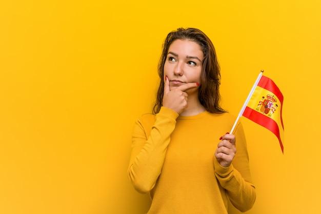 Junge europäische frau, die eine spanische flagge seitlich schaut mit zweifelhaftem und skeptischem ausdruck hält.