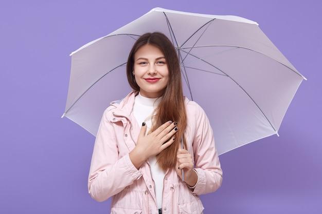Junge europäische frau, die einen regenschirm hält, der über fliederwand isoliert ist, hand auf brust hält, lächelt aufrichtig, dankbar, drückt ihre angenehme haltung aus.