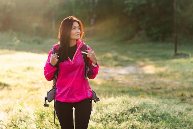 Junge europäische frau, die mit rucksack auf grüner wiese nahe wald geht. attraktives fokussiertes mädchen trägt sportkleidung und rosa jacke. konzept der erholung und des tourismus in der natur. sonniger tag