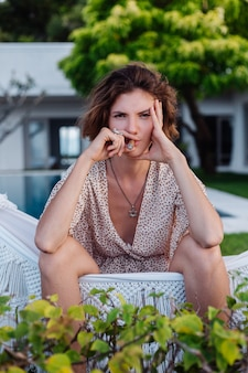 Junge europäische frau, die zigarre raucht, die auf hängematte außerhalb des tropischen luxusvillenhotels liegt, natürliches licht des sonnenuntergangs