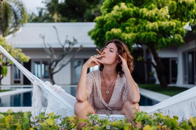 Junge europäische frau, die zigarre raucht, die auf hängematte außerhalb des tropischen luxusvillenhotels liegt