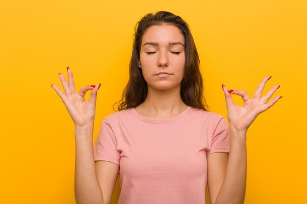 Junge europäische frau entspannt sich nach hartem arbeitstag, sie führt yoga durch.