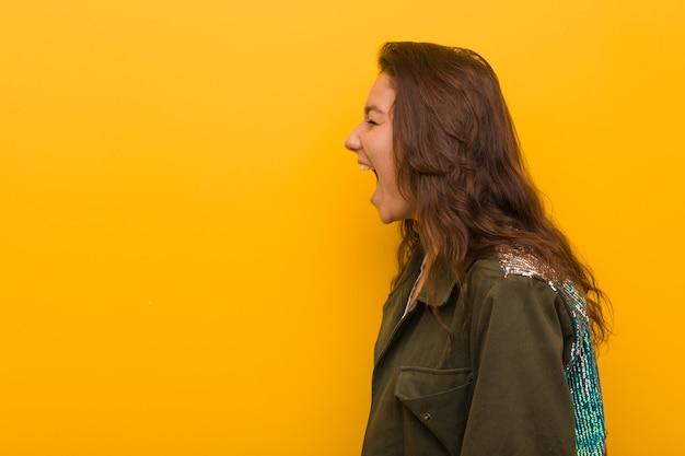 Junge europäische frau getrennt über dem gelben schreien in richtung zu einer kopie