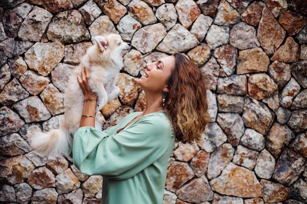 Junge europäische frau im romantischen sommerkleid-armband hält niedlichen flauschigen pommerschen welpenspitz außerhalb der villa