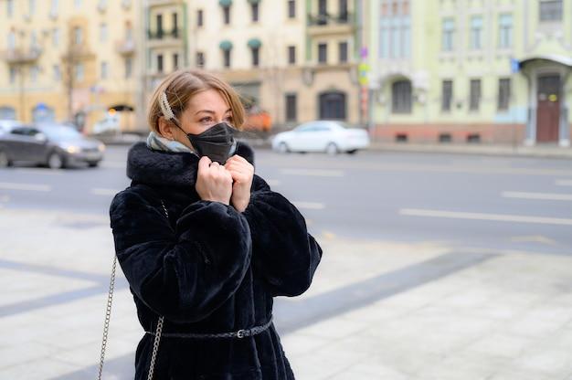 Junge europäische frau in der medizinischen schwarzen einwegmaske des schutzes in der stadt im freien