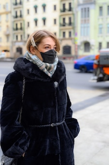 Junge europäische frau in der medizinischen schwarzen einwegmaske des schutzes in der stadt im freien.