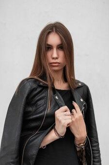 Junge europäische frau in einem eleganten kleid begradigt eine stilvolle schwarze lederjacke in der nähe eines weißen vintage-gebäudes. sexy hübsches schönes mädchenmodemodell, das auf einem weißen hintergrund aufwirft. herbststil.
