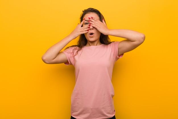 Junge europäische frau isoliert über gelbe wand blinken durch finger erschrocken und nervös.