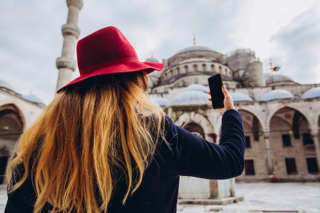 Junge europäische frau nimmt ein selbstporträt in istanbul, türkei. mädchen geht durch den winter istanbul. blondine macht ein foto am telefon vor dem hintergrund einer moschee am herbsttag.