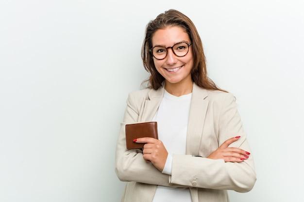 Junge europäische geschäftsfrau, die ein geldbörsenlächeln überzeugt mit den gekreuzten armen hält.