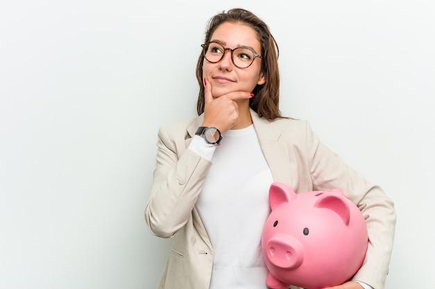 Junge europäische geschäftsfrau, die ein sparschwein seitlich schaut mit zweifelhaftem und skeptischem ausdruck hält.