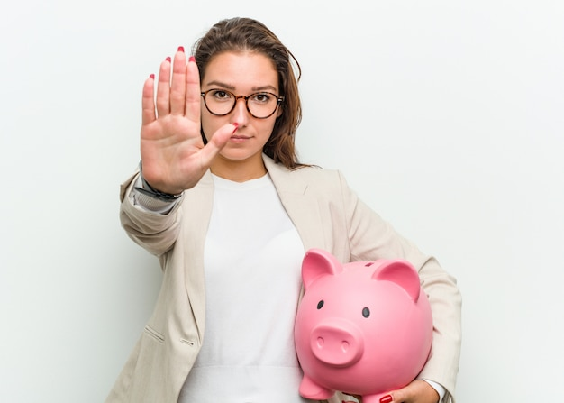 Junge europäische geschäftsfrau, die ein sparschwein steht mit der ausgestreckten hand zeigt das stoppschild und verhindert sie hält.