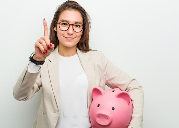 Junge europäische geschäftsfrau, die ein sparschwein zeigt nummer eins mit dem finger hält.