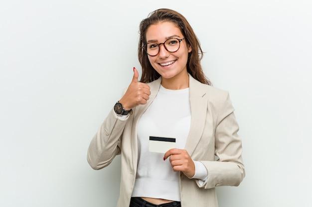 Junge europäische geschäftsfrau, die eine kreditkarte lächelt und angehoben daumen hält