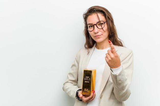 Junge europäische geschäftsfrau, die einen goldbarren zeigt mit dem finger auf sie hält, als ob einladung näher kommen.