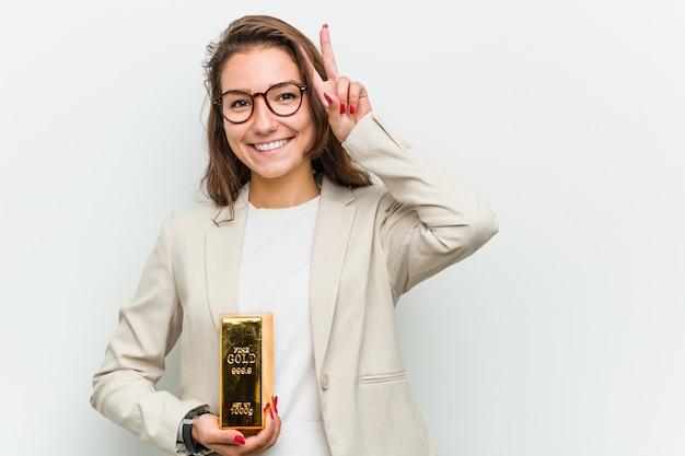 Junge europäische geschäftsfrau, die einen goldbarren zeigt siegeszeichen und breit lächelt hält.