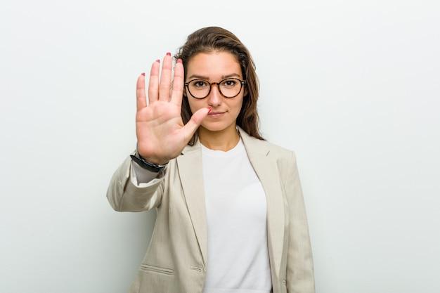 Junge europäische geschäftsfrau, die mit ausgestreckter hand steht, die stoppschild zeigt, das sie verhindert.