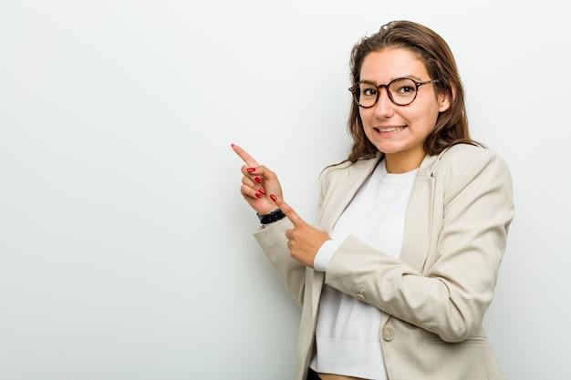 Junge europäische geschäftsfrau entsetzte das zeigen mit den zeigefingern auf eine kopie.