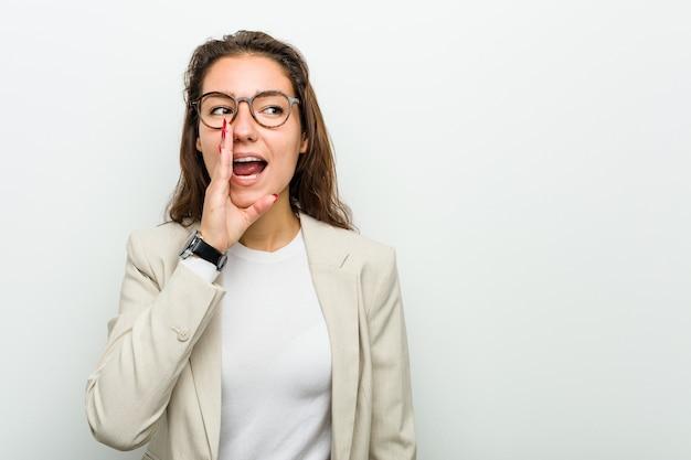 Junge europäische geschäftsfrau sagt eine geheime heiße bremsnachricht und schaut zur seite