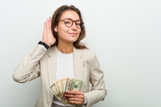Junge europäische geschäftsfrau, welche die dollarbanknoten versuchen, einen klatsch zu hören hält.