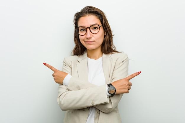 Junge europäische geschäftsfrau zeigt seitwärts, versucht, zwischen zwei wahlen zu wählen.