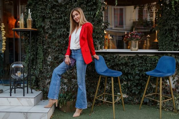 Junge europäische selbstbewusste frau mit offenem lächeln, das draußen in der bar aufwirft. trägt eine rote modische jacke