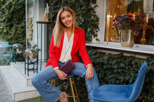 Junge europäische selbstbewusste frau mit offenem lächeln, das draußen in der bar aufwirft