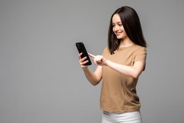 Junge europäische studentin scrollt mit konzentriertem ausdruck in ihrem smartphone nach nachrichten