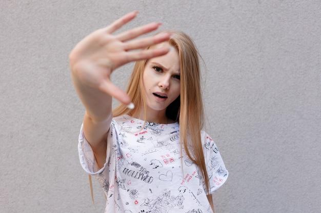 Junge europäische trendige frau mit wütendem unzufriedenem ausdruck, die hand in stop-geste hält und versucht, ihr gesicht vor der kamera zu bedecken, isoliert auf weißem hintergrund. es ist schwer ein berühmtes model zu sein