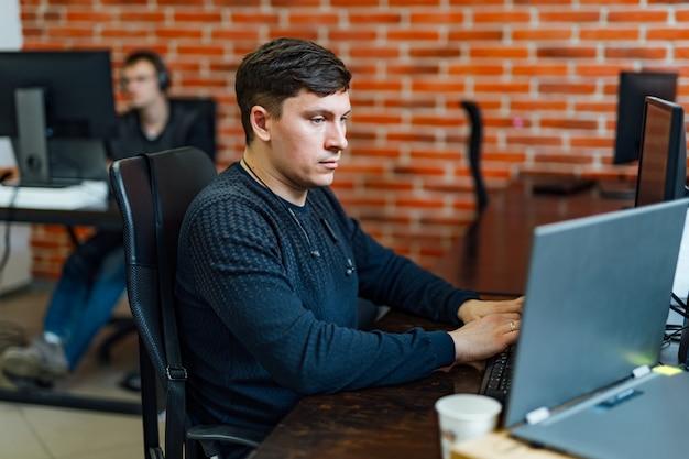 Junge exekutive, die an seinem schreibtisch mit dem laptop liest ein dokument sitzt.