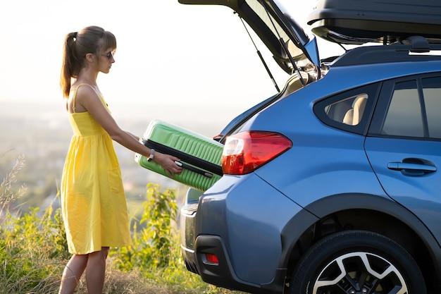 Junge fahrerin, die grünen koffer aus dem kofferraum des autos herausnimmt. reise- und urlaubskonzept.