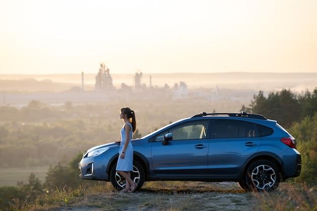 Junge fahrerin, die nahe ihrem auto ruht und warmen sommerabend genießt. reise- und fluchtkonzept.