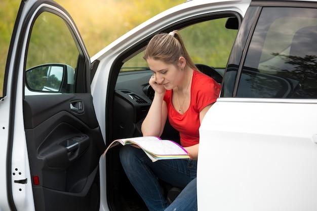 Junge fahrerin hat sich beim fahren auf dem land verirrt und die karte gelesen, um die route zu finden