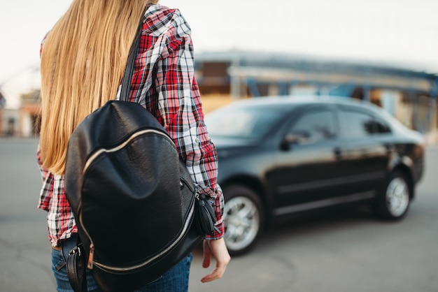 Junge fahrerin mit tasche gegen ein auto